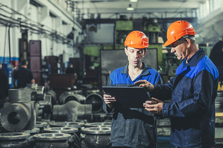 Two engineers on the floor of a manufacturing plant