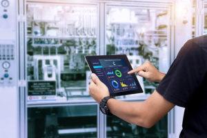 Smart industry control concept. Hands holding tablet on blurred automation machine as background.